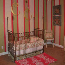 Pink white and green French baby girl nursery with iron crib and gold wall letters