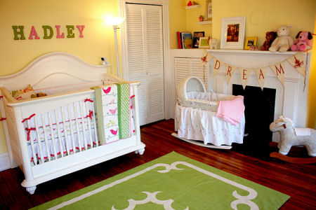 Baby girl bird theme nursery in pink and yellow with painted wall stripes