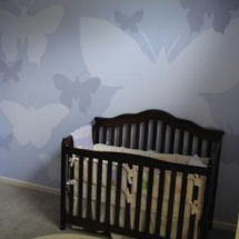 Modern blue baby girl butterfly nursery with crib and butterfly wall painting technique
