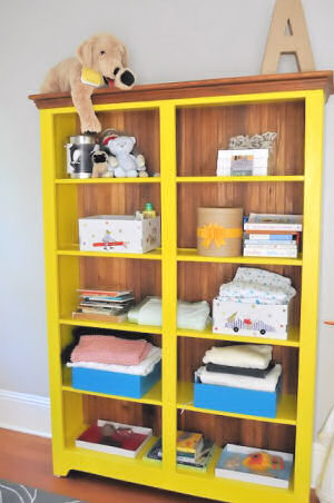 Bright yellow bookshelf painted with Confident Yellow Sherwin Williams paint