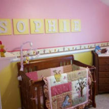 Pink and yellow baby girl Winnie the Pooh nursery with her name in wooden wall letters