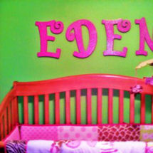 Hot pink painted wooden letters spelling a baby girl's name on neon lime green nursery wall