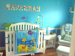 Baby girl purple whale ocean wonders theme nursery room with blue walls and custom wooden wall letters to match the crib set