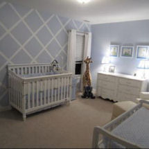 Baby blue green and white boy nursery with painted lattice pattern on an accent wall