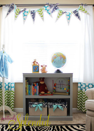 Homemade pennant banner made with custom fabrics for a baby's nursery window treatment.