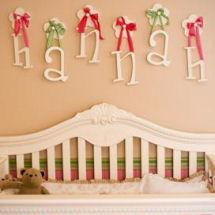 Wooden wall letters for a pink and green nursery that spell a baby girl's name hung by ribbons