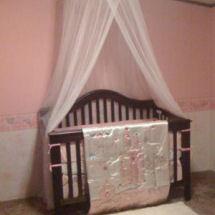 Pink princess nursery with a white gauze princess crown canopy and satin crib set