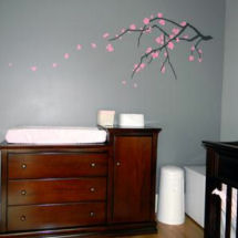 Peaceful gray and pink baby girl nursery with pink floral tree branch wall mural
