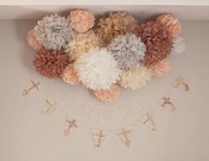 Peach taupe ivory white and gray tissue paper pom poms in the baby's nursery