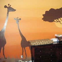 Safari jungle baby nursery theme with gold wall paint and chocolate brown giraffe and African Tree silhouette art with zebra print crib bedding and curtains