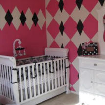 White, pink and black baby girl nursery room with unique argyle wall painting technique