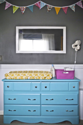 This baby girl's nursery has charcoal gray walls accented with bright colors including a turquoise blue dresser.