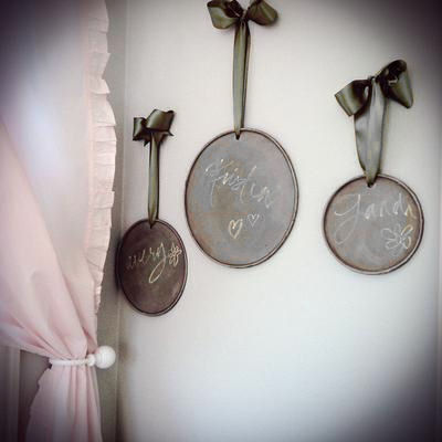 A wall display of Restoration Hardware chalkboards hung with wide, chocolate brown satin ribbons tied in bows in a baby girl nursery