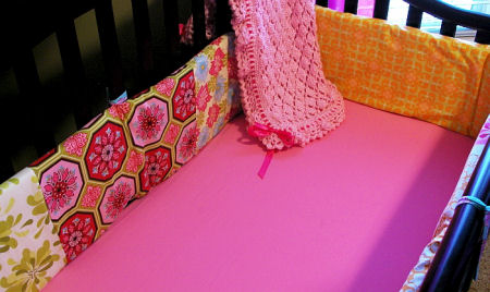 Bright colorful hot pink and orange custom crib bedding set with touches of green aqua and solid pink fitted crib sheet in a creative nursery