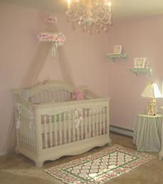 DIY baby bed canopy decorated with a wreath of silk roses in a baby girl nursery room