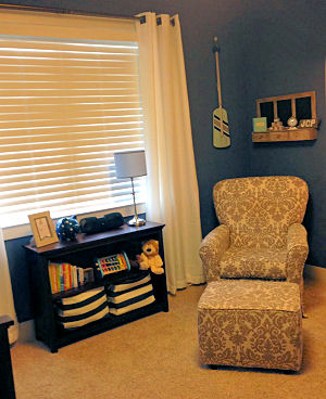 Comfortable seating and efficient storage in a baby boy nautical nursery with a navy blue wall paint color