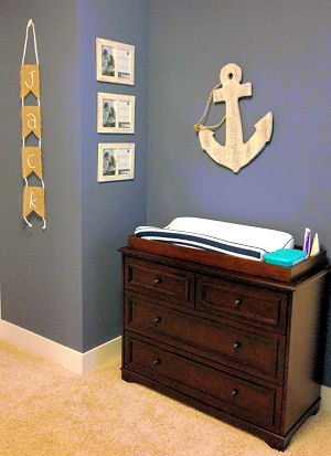 A rustic wooden anchor wall decoration in the changing area of a baby boy nautical nursery room