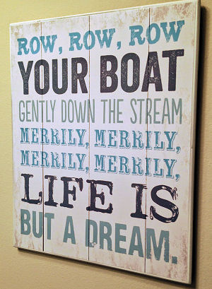 A  rustic sign with a line from the popular row row row your boat nursery rhyme used as wall décor in a baby boy nautical nursery