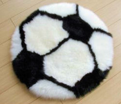 Black and white soccer ball sheepskin baby rug for a sports theme nursery
