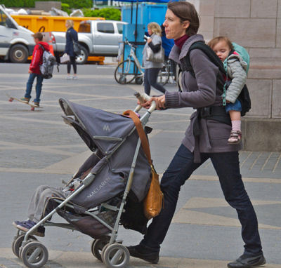 mom in central park with baby stroller and baby backpack