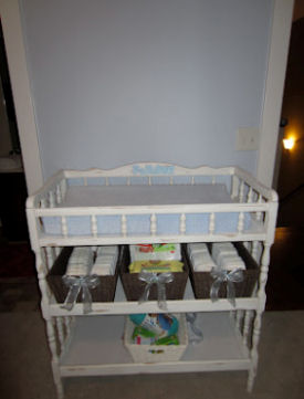 White diaper changing station with storage baskets on shelves underneath