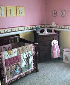 pink and yellow Winnie the Pooh decorated nursery crib bedding and décor for a baby girl