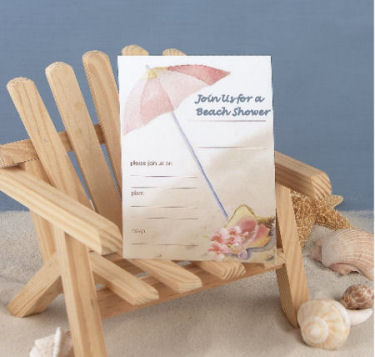Beach theme baby shower invitation on a wooden adirondack chair in the sand surround by seashells under an umbrella by the ocean in pink and blue for baby girls or boys