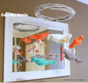 DIY Baby nursery crib mobile with a grapevine wreath nest frame and stuffed birds made of custom fabrics