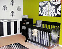 Black and white stripes painted on a baby girl nursery wall with a polka dot border