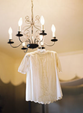 Vintage baby dress on a hanger displayed on an antique chandelier in a nursery setting