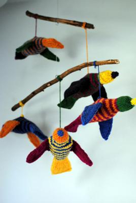 Here's a closeup picture of the hand-knitted tropical bird baby mobile that is displayed over the baby's changing table in the nursery.