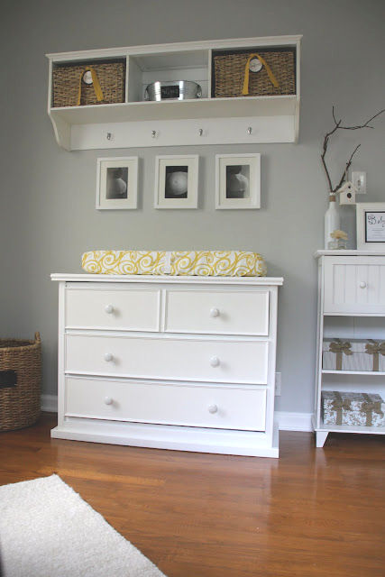 A white dresser changing table a pad covered in modern yellow and white fabric