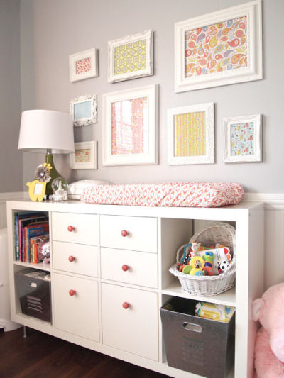baby girl neutral gray nursery wall with wall arrangement of colorful framed fabric