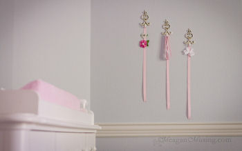 Shabby chic ivory hooks used to display baby girl hair bows on the nursery wall