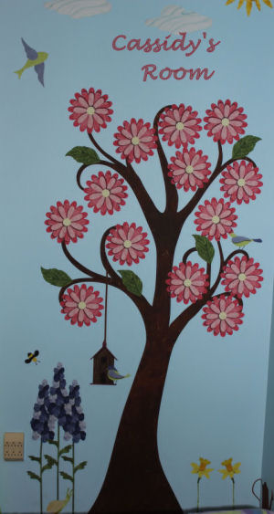 Large tree decal decorated with flowers, leaves and birds in baby girl's room.