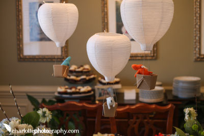 DIY hot air balloon baby shower and nursery decorations made from paper lanterns with toy animals in the basket