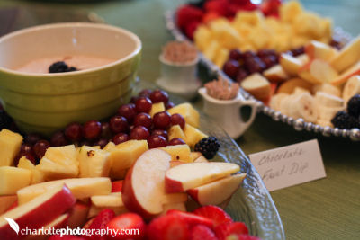 Fruit and chocolate dip complement the savory treats on the baby shower snack menu