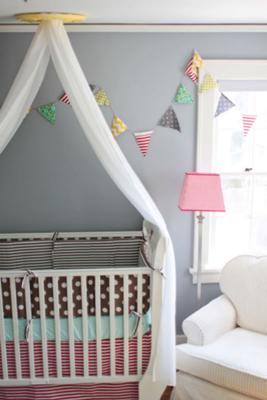 A shared baby nursery with colorful pennants and crib bedding set