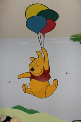 A closeup view of Pooh Bear taking a balloon ride