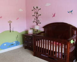 Pink dragonfly baby girl nursery ideas with frogs birds and a personalized name sign on the wall