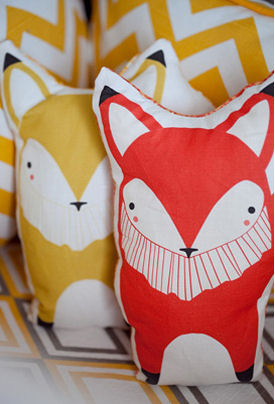 A pair of colorful stuffed toy foxes in red and yellow