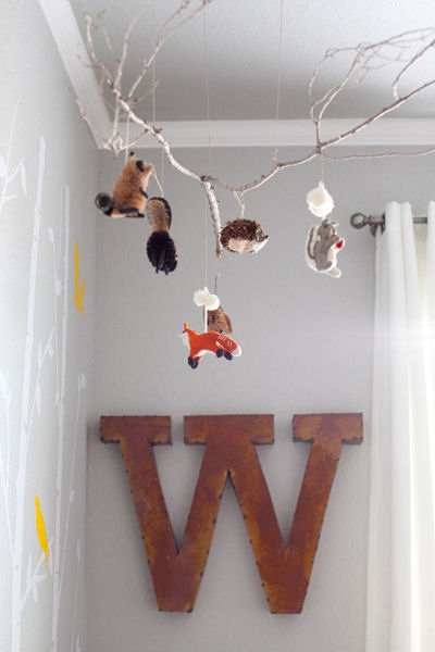 The woodland creatures animal themed baby crib mobile made with a real tree branch is decorated with red fox racoons squirrels beaver and porcupine