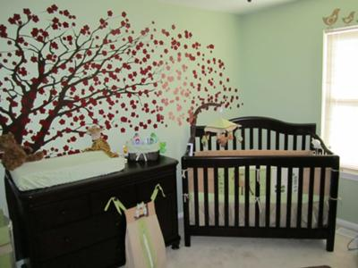 Mystical forest baby nursery theme.  The baby's room has its own cherry tree wall mural surrounded with baby deer, birds and other woodland creatures.  The soft sage green nursery walls make the space so peaceful.
