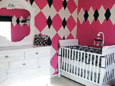 Pink black and white French baby girl nursery with a harlequin accent wall
