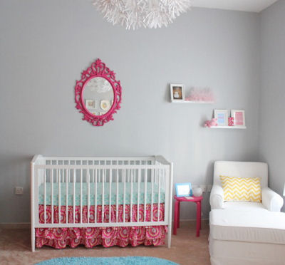 Pops of bright fuchsia pink in this baby girl's nursery are the perfect complement for the soft, grey nursery wall paint color.