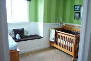 The window in the baby's nursery with decorative ABC accent pillows and chocolate brown cushion
