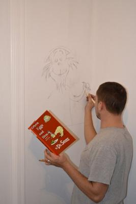 Dad making sketches of our favorite Dr. Seuss illustrations on the nursery wall