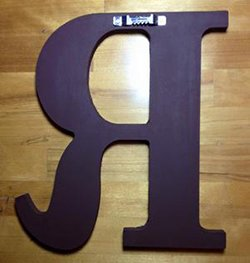 Back of a custom made hand painted wooden wall letter with hanger