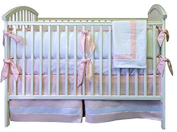 Tailored pink and white bedding set for a baby girl with a crib skirt made with box pleats