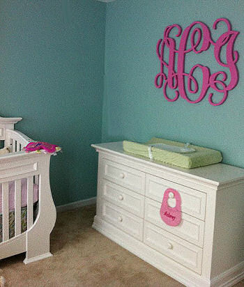 Elegant pink teal and white baby girl nursery room with large painted wooden wall letters featuring a baby girl's initials in  a circular monogram